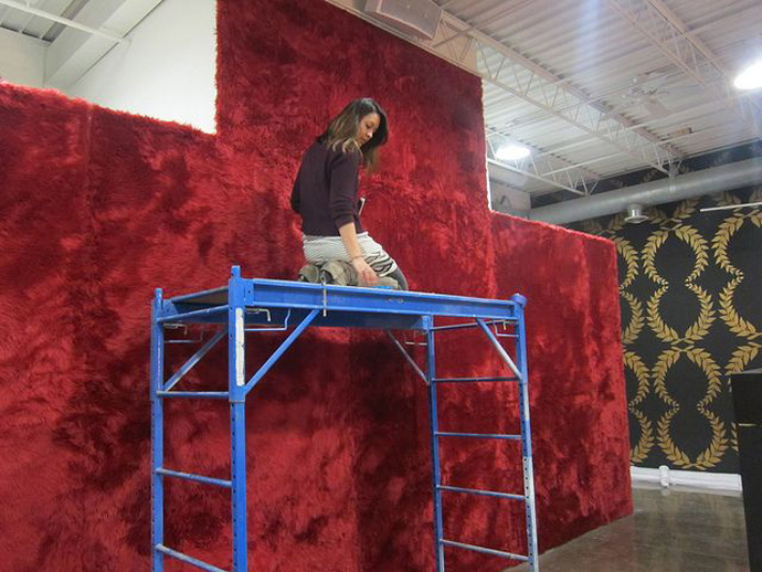 Curator Tricia Khutorestsky installing red shag carpet on the wall for Dzine - Victory (Photo courtesy of Public Functionary)